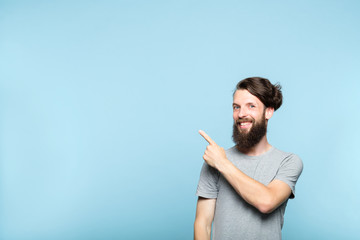 young man pointing left and above his head to a virtual object or text. copy space for advertisement or product placement. portrait of a bearded hipster guy on blue background.