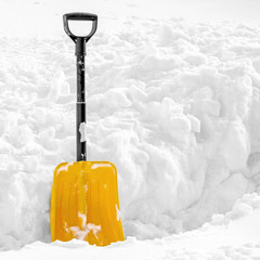 Yellow plastic shovel stuck upright in fluffy pile of white snow in winter. Picture with copy space on the right