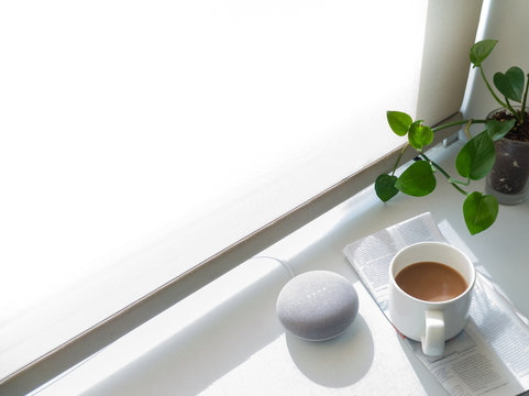 A smart speaker on a window bay with coffee and a newspaper. Smart home. Morning routine.