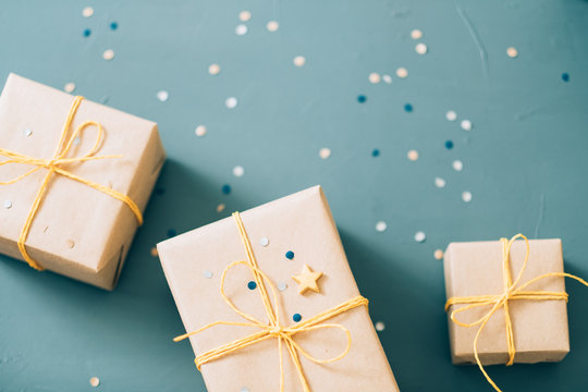 handcrafted present. gifts wrapped in craft paper and tied with yellow twine. festive boxes on blue background with confetti decor. holiday celebration and congratulation.