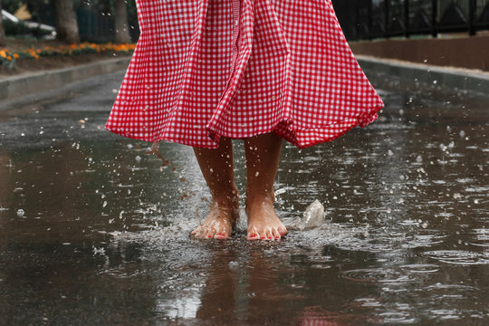 close-up of a girl's feet dancing in a puddle after a summer rain