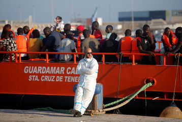 A rescuer waits as migrants are seen after disembarking a rescue boat at the port of Malaga
