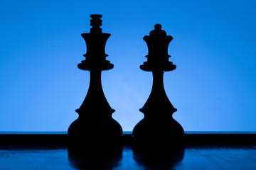 King and Queen chess pieces silhouettes standing side by side on a blue background