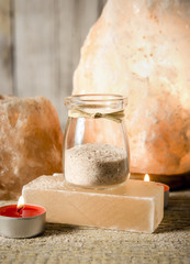 Himalayan salt grains in cute round glass jar on wooden background. Blocks salt used as serving dishes.
