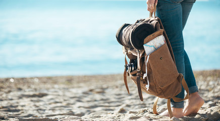 Woman traveler stand on the sand beach and holding backpack. Concept of travel.