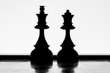 King and Queen chess pieces silhouettes standing side by side on a white background