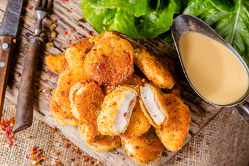 Fresh pile of crispy home-baked chicken nuggets and sauce on a wooden background, blackboard, rustic style, fork and knife, with mustard sauce, and with spices, Closeup