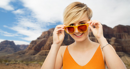 travel, tourism and summer holidays concept - portrait of happy smiling young woman in sunglasses over grand canyon national park background