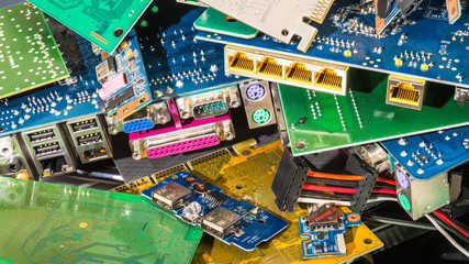 E-waste pile from discarded computer parts. Colorful background from PC components. Mainboards, PCB, connectors. Idea of hardware, electronics industry, eco, sorting and disposal of electronic waste.