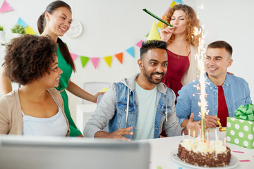 corporate, celebration and people concept - happy business team with birthday cake and gifts greeting male colleague at office party