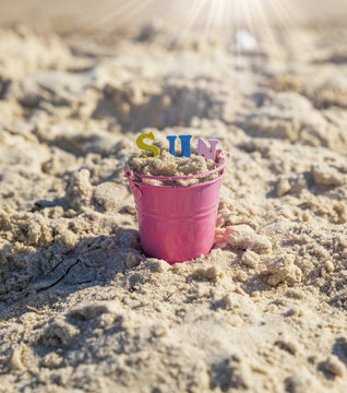 pink baby iron bucket filled with wooden colorful letters stands on the sand