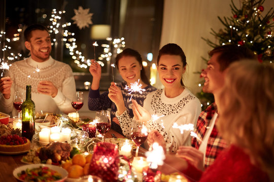 winter holidays and people concept - happy friends with sparklers celebrating christmas at home feast