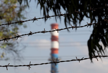 A chimney of the ILVA steel plant is seen behind  barbed wire in Taranto