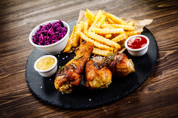 Grilled drumsticks with french fries and vegetables on wooden background