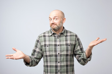 Portrait of confused mature man d standing over white background gesturing with hands.