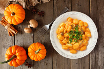 Gnocchi with a pumpkin, mushroom cream sauce. Autumn meal. Above view table scene on a wood background.