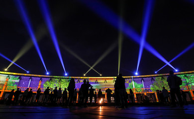 People look at a light installation on the World War Two museum during the Circle of Light International Festival in Moscow