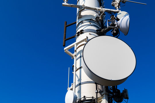 An close-up image of a telecommunications dish on a tower on a blue background