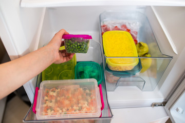 Woman taking container with frozen mixed vegetables from refrigerator.