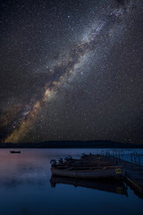 Vibrant Milky Way composite image over landscape of still lake with boats on jetty