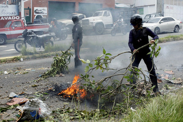 Police officers remove debris used by demonstrators to block a street during a protest due to the gas shortage in San Cristobal