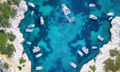Yachts at the sea in France. Aerial view of luxury floating boat on transparent turquoise water at sunny day. Summer seascape from air. Top view from drone. Seascape with motorboat in bay.