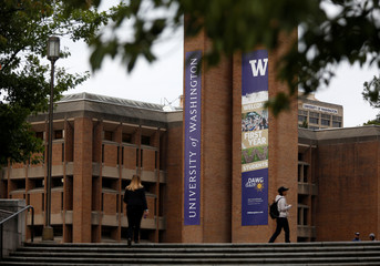 People walk by large welcome banners at Red Square at the University of Washington in Seattle Washington
