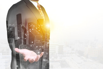 Double exposure image of businessman standing with open hand overlay with cityscape image