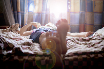 close up young male lying on bed sleep in the mroning against the sunshine throung the window f