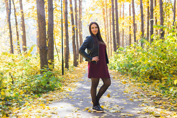 Autumn, nature, people concept - young beautiful woman walking in autumn park in red dress and black jacket