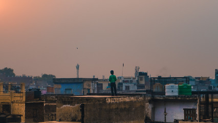 Boy on rooftop of Old Dehli looking at the sunset sky