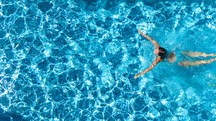 Aerial drone view of active girl in swimming pool from above, yong woman swims in blue water, tropical vacation, holiday on resort concept