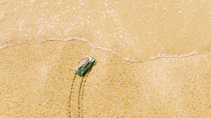 A symbolic car at the edge of the sea in the sand