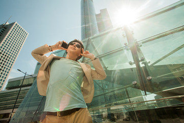 Travel and lifestyle concept. Fashion man listening to music on phone and dancing against the background of skyscrapers.