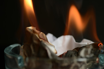 A piece of paper burning in a glass ashtray close up