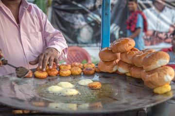 Close shot of frying aloo tikki and bread, Indian street food