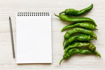 Green chili peppers and blank notebook on white wooden surface, top view. Flat lay, overhead, from above. Space for text.