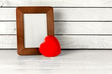 Photo Frame with Red Heart on table over white wood background