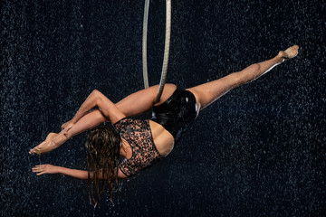 A young flexible girl performs the splits in the aerial ring. Aqua Studio shooting performances on a black background