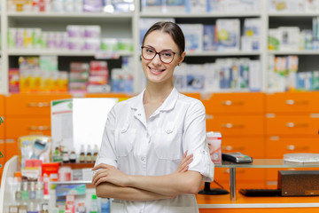 A smiling beautiful girl with dark hair and glasses,wearing a medical overall,stands by the cash desk with her arms crossed  in a modern pharmacy.
