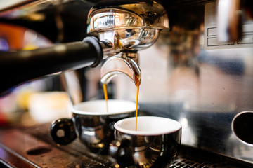 Close-up of espresso pouring from coffee machine into cups. Professional coffee brewing, barista details