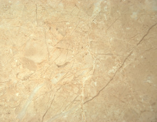 Decorative surface, beige marble with white veins. A close-up shot.