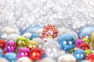 Christmas and New Year's toy fairy tale red house in snowdrifts and snow of Christmas balls and tinsel in different bright colors, holiday decorations, ornaments, lights, bokeh close up macro