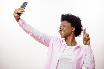 awesome positive hipster girl showing victory sign while making selfie on the smart phone. close up side view portrait, white background
