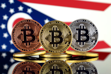 Physical version of Bitcoin (BTC) and Ohio State Flag. Conceptual image for investors in High Technology (Cryptocurrency, Blockchain Technology, Smart Contracts, ICO).