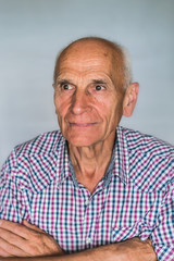 An elderly man crossed his arms, looking away.