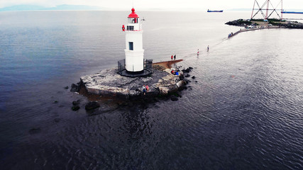 Top view of the lighthouse standing in the sea. small lighthouse with red roof