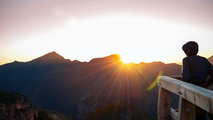 Young person in a raincape watching the sunrise in the mountains