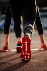 Rear view of runner foot at start of track at the stadium