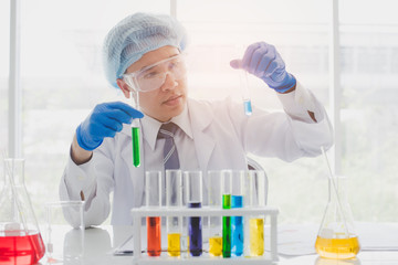 Senior scientist are examining the results with a test tube in a science lab. Researcher working in the laboratory.